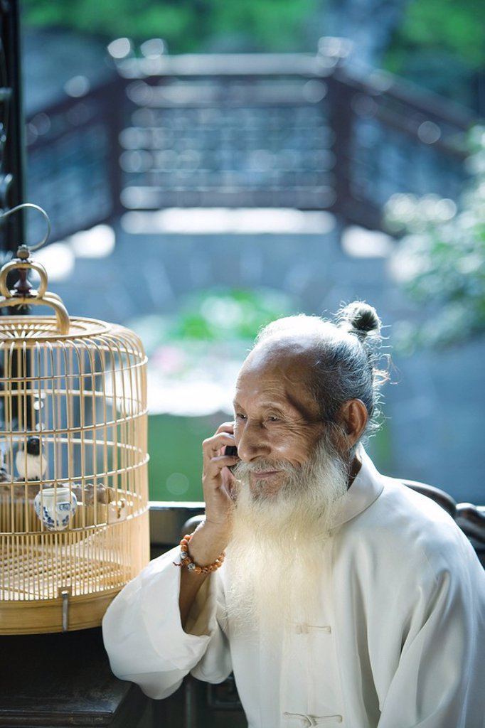 Elderly man wearing traditional Chinese clothing, using cell phone, next to bird cage : Stock Photo