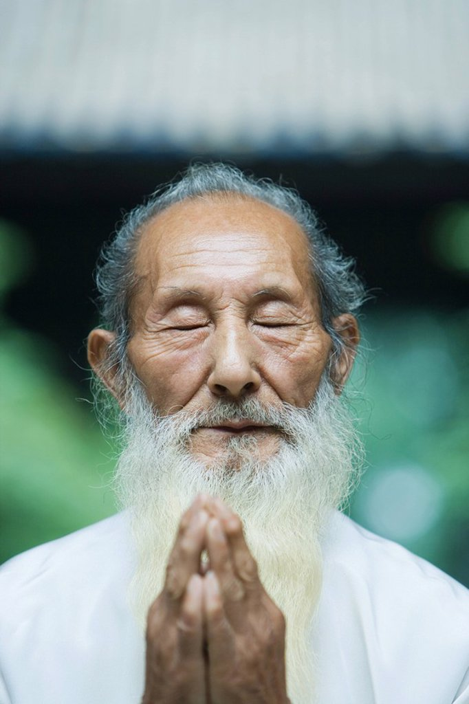 Elderly man praying : Stock Photo