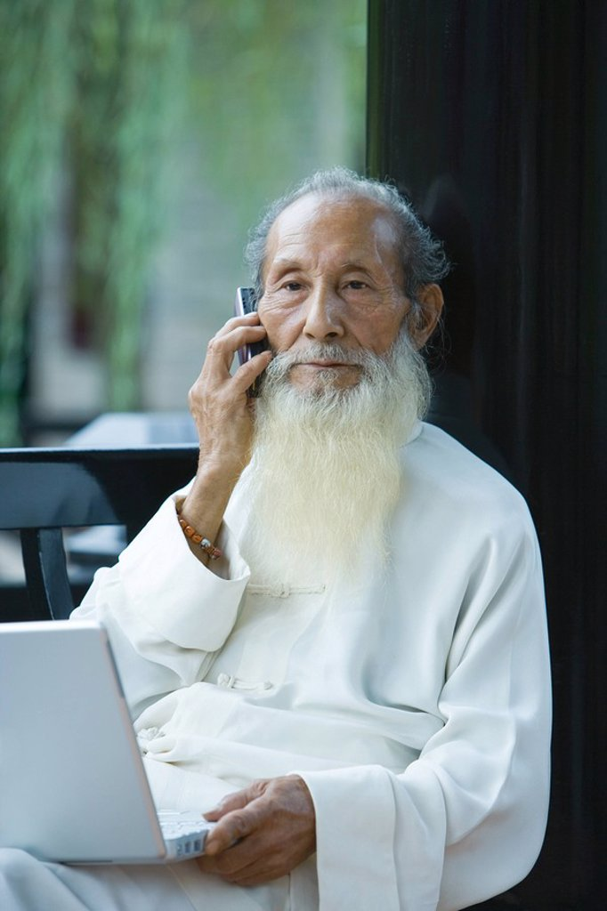 Elderly man wearing traditional Chinese clothing, using laptop and cell phone : Stock Photo