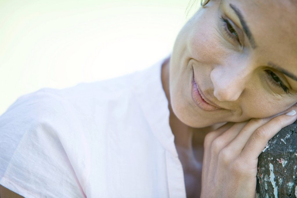 Stock Photo: 1747R-7512 Woman leaning head on wooden post, smiling, looking away, close-up