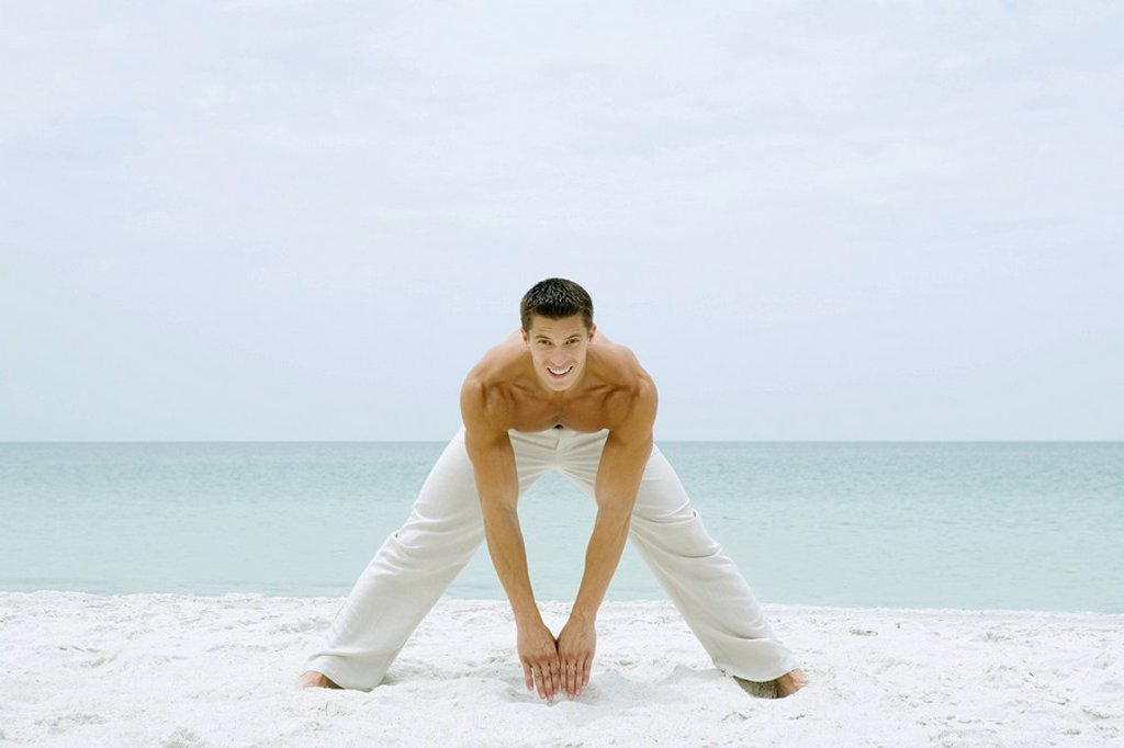 Man standing on beach, stretching and smiling at camera, full length : Stock Photo