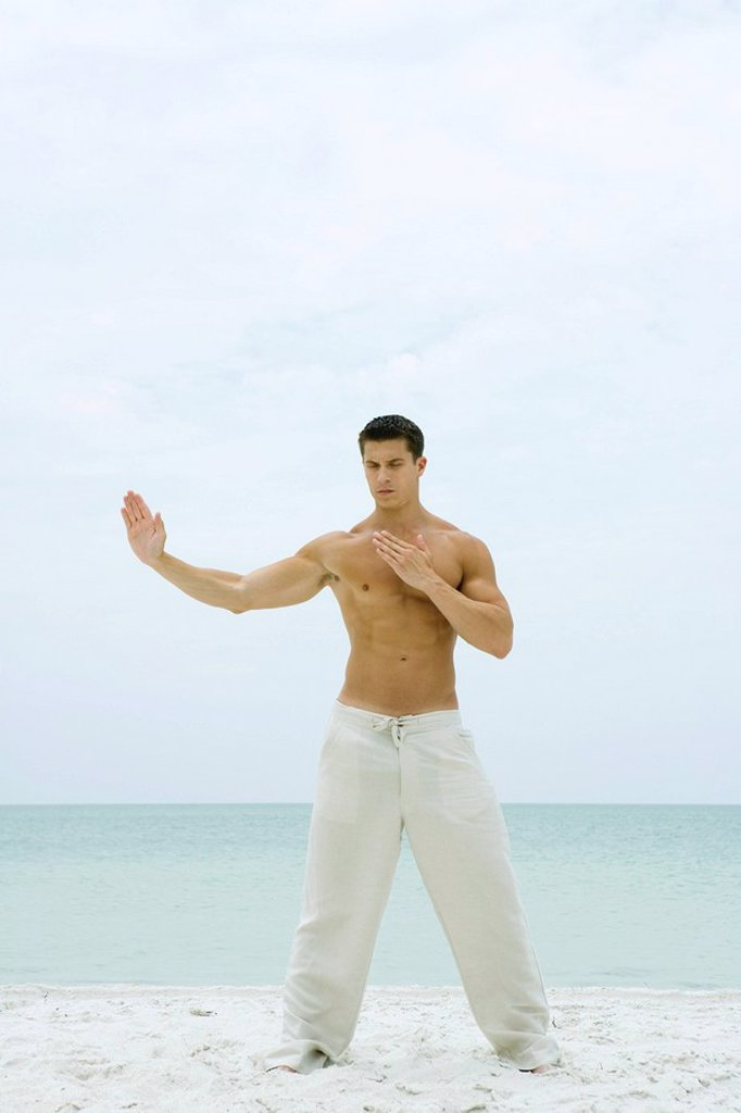 Stock Photo: 1747R-7802 Man standing on beach, doing tai chi, full length
