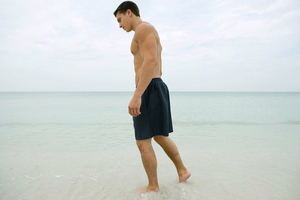 Stock Photo: 1747R-7809 Man standing in surf, full length