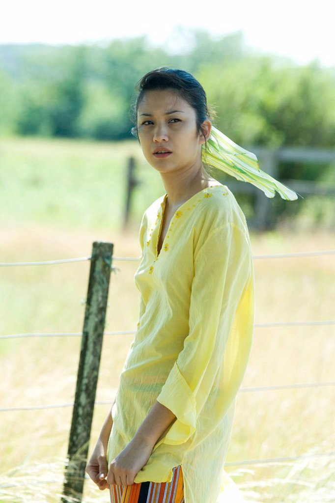 Young woman standing by rural fence : Stock Photo