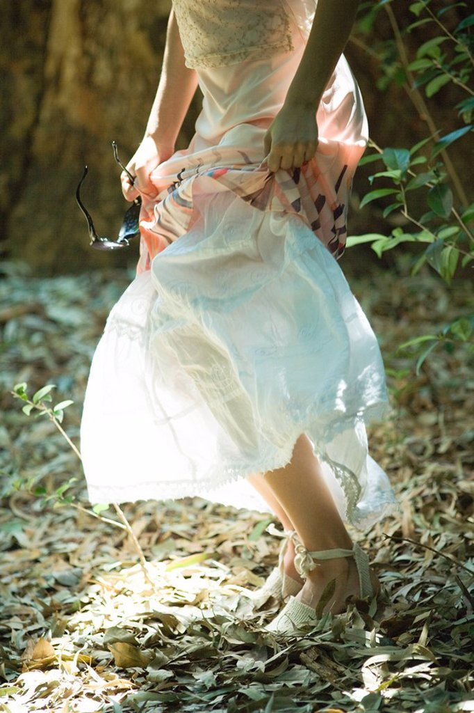 Stock Photo: 1747R-7852 Young woman standing in woods, lifting up skirt, waist down