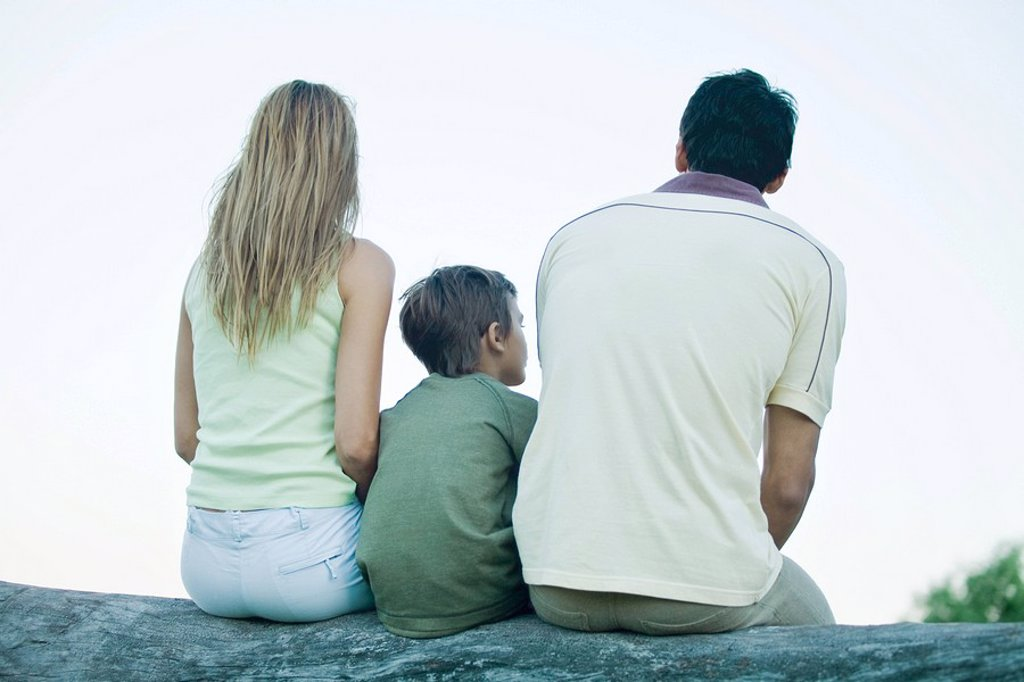 Stock Photo: 1747R-7977 Boy with parents, sitting on log, rear view