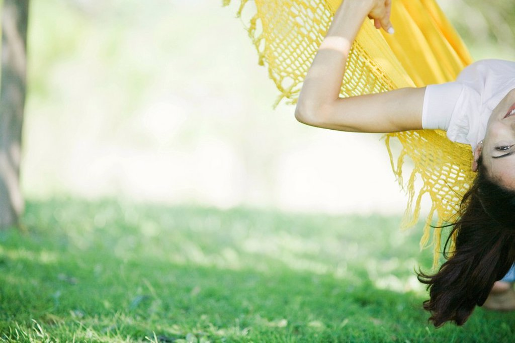 Stock Photo: 1747R-8004 Woman lying on hammock with head hanging upside down, partial view