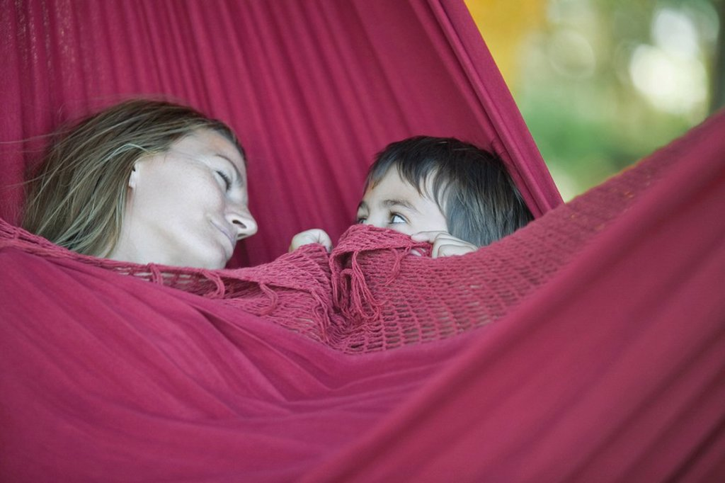 Stock Photo: 1747R-8011 Mother and son lying in hammock, woman sleeping, boy peeking at woman