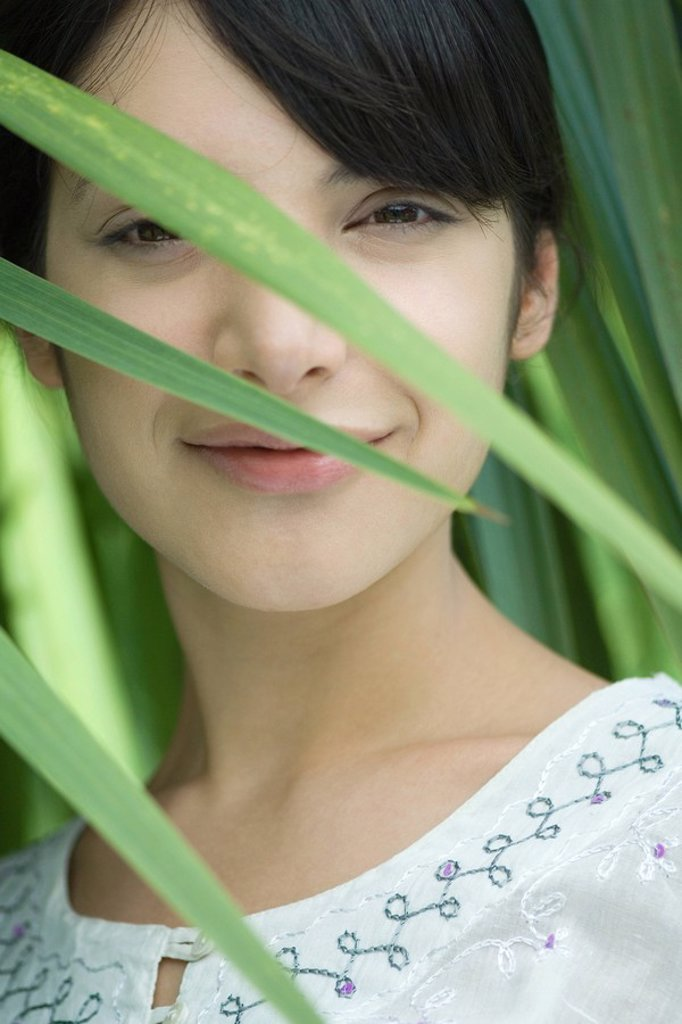 Stock Photo: 1747R-8055 Woman smiling at camera through foliage, portrait