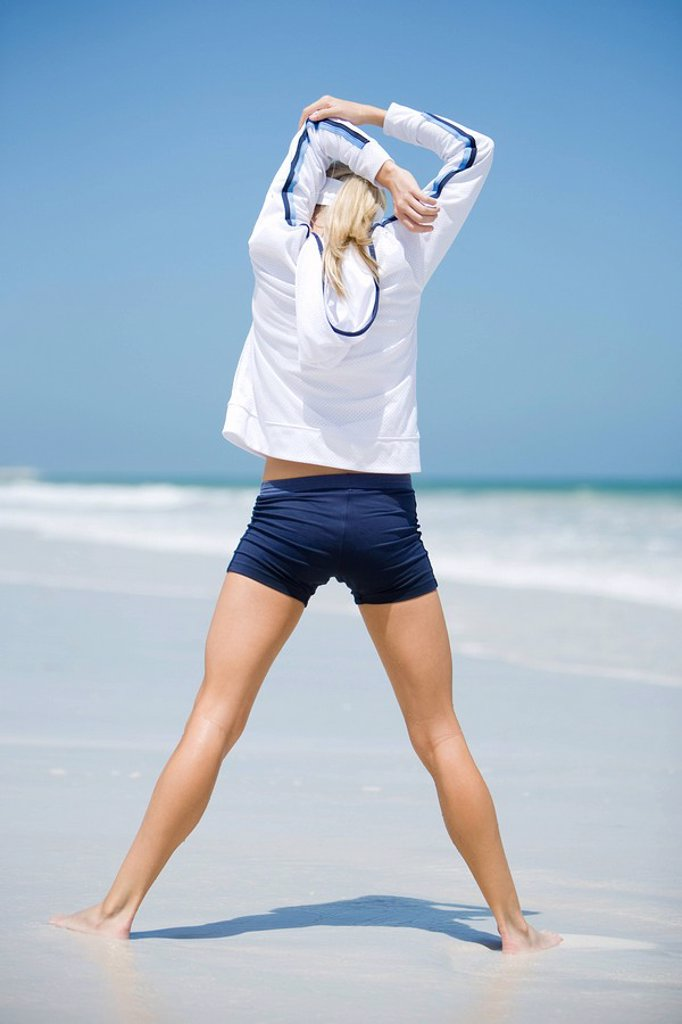 Young woman on beach, stretching, rear view : Stock Photo