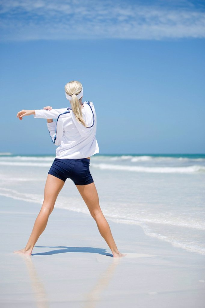 Stock Photo: 1747R-8294 Young woman on beach, stretching, rear view