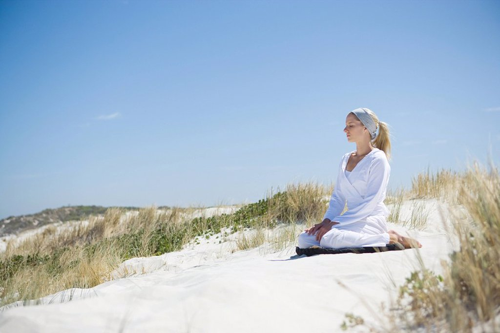 Young woman meditating on beach : Stock Photo