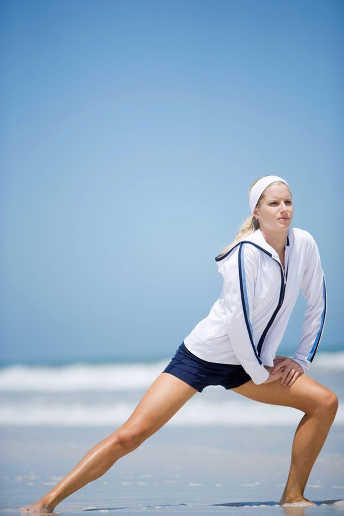Young woman on beach, stretching : Stock Photo