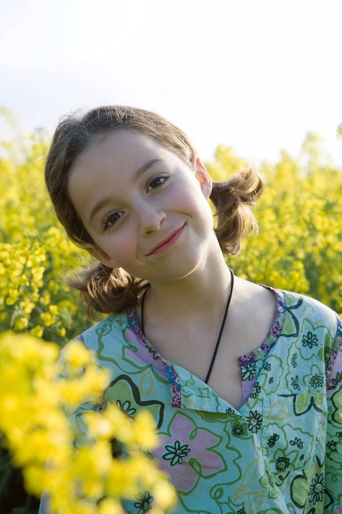 Girl standing in field of canola in bloom, smiling at camera, portrait : Stock Photo