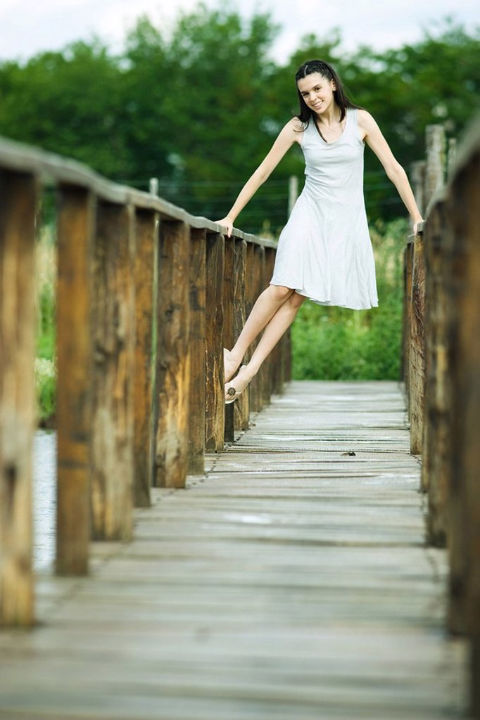 Teen girl lifting self up on railing of wooden bridge, smiling at camera : Stock Photo