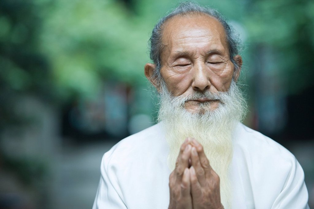 Elderly man in traditional Chinese clothing, hands clasped in prayer : Stock Photo