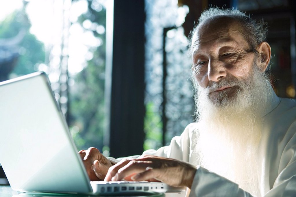 Elderly man in traditional Chinese clothing using laptop computer : Stock Photo