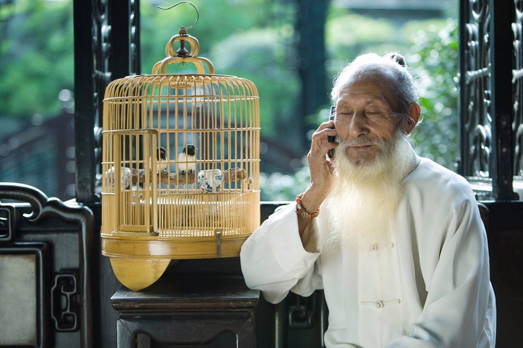 Elderly man in traditional Chinese clothing holding cell phone to ear, sitting next to bird cage : Stock Photo
