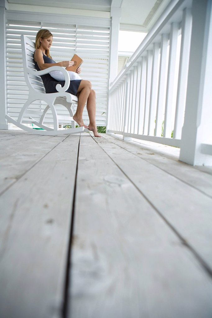 Stock Photo: 1747R-8578 Woman sitting in rocking chair on porch, reading book, low angle view