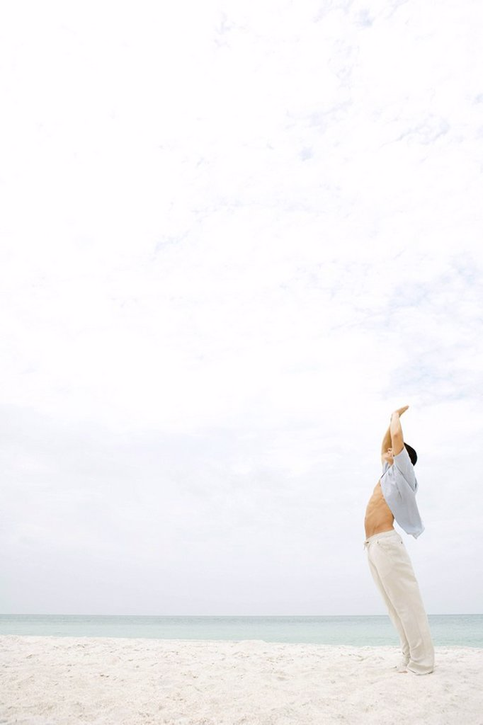 Man standing in sun salutation pose on beach, side view : Stock Photo