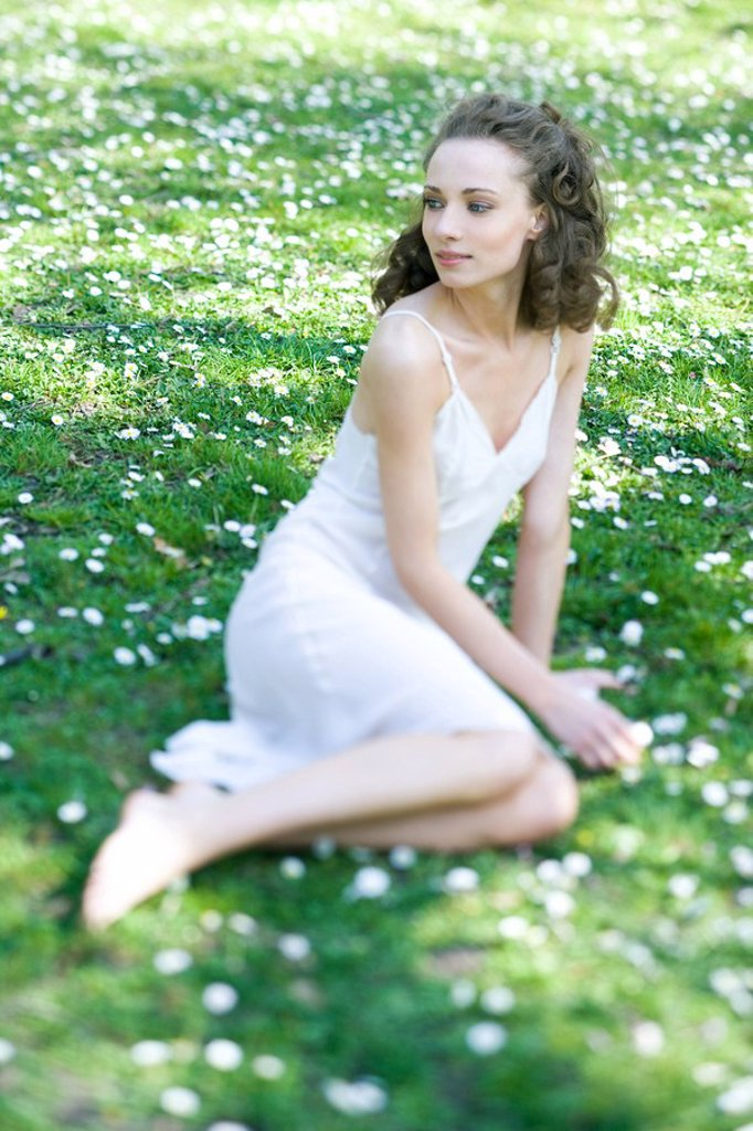 Stock Photo: 1747R-8863 Young woman wearing slip, sitting in field of flowers, looking over shoulder, smiling