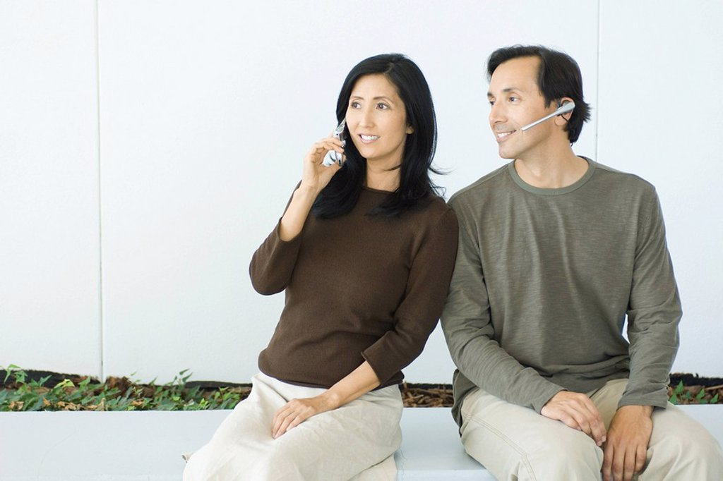 Couple sitting side by side, woman using cell phone, man wearing headset, both smiling : Stock Photo