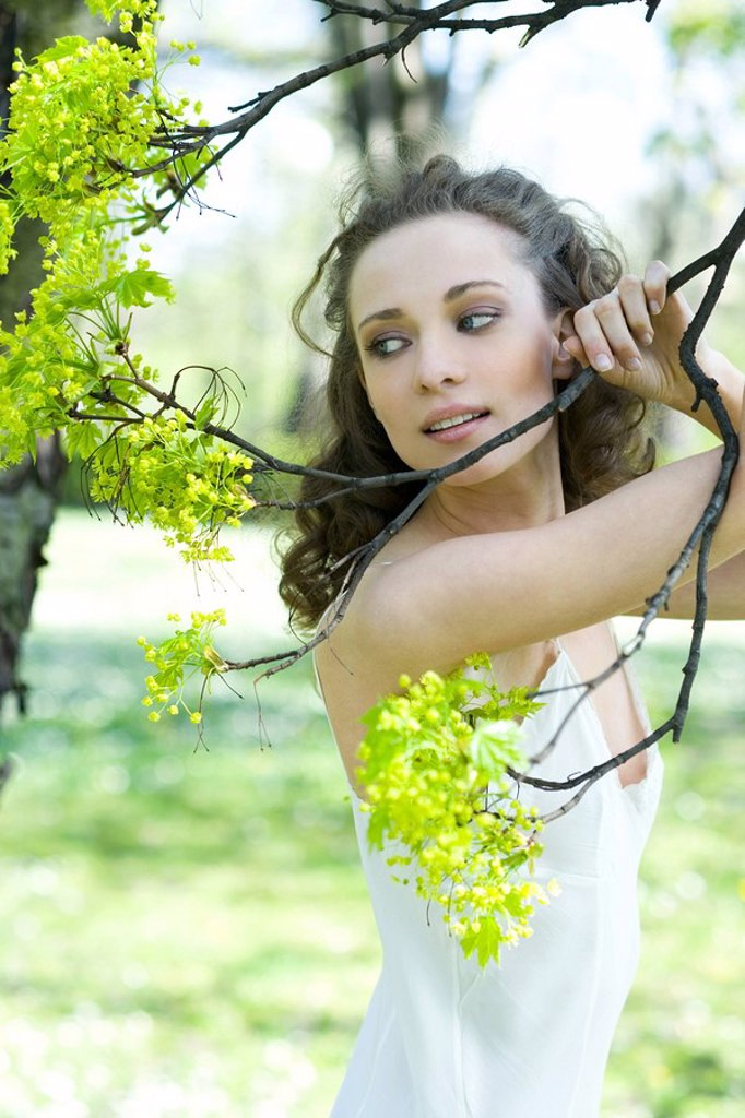 Young woman holding flowering tree branch, looking away : Stock Photo