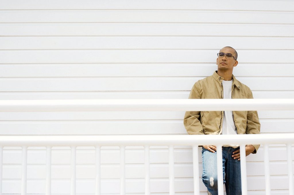 Stock Photo: 1747R-9834 Man leaning against wall, hands on hips, looking away