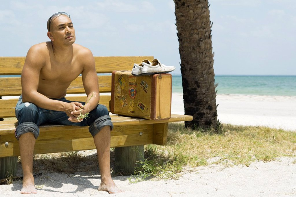 Man sitting on bench at the beach, suitcase beside him, looking away : Stock Photo