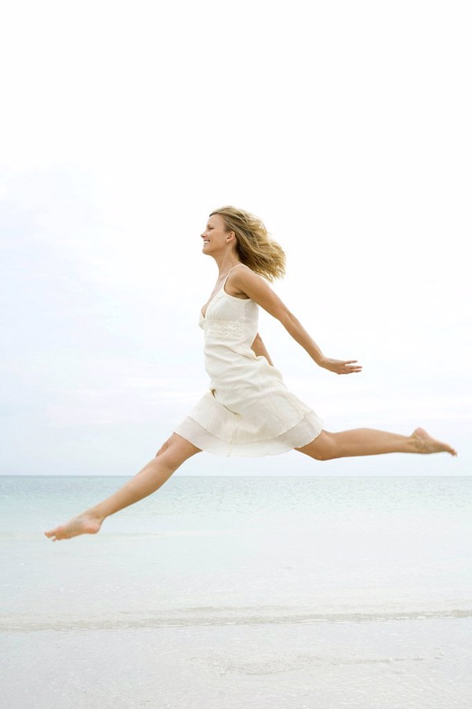 Woman jumping in the air at the beach, side view : Stock Photo