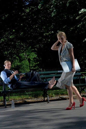 Stock Photo: 1755-145D Businesswoman walking with a businessman reclining on a park bench