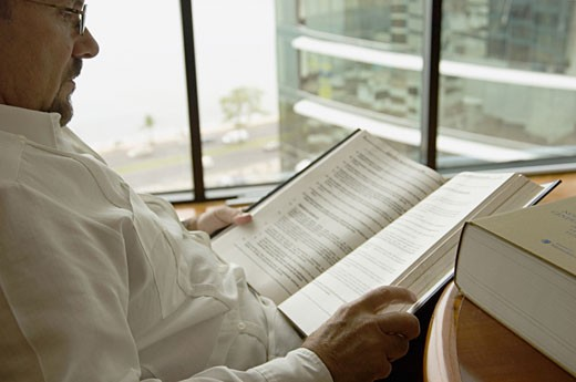 Stock Photo: 1757R-1043 Businessman reading book in office.