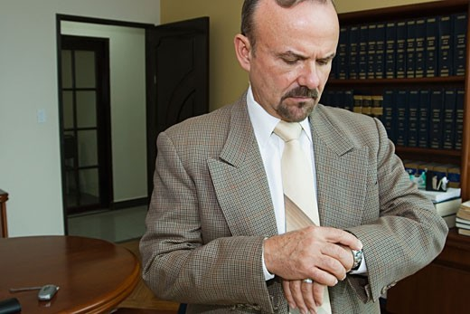 Businessman checking the time on his watch : Stock Photo