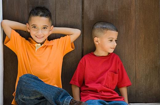 Two boys sitting in doorway. : Stock Photo