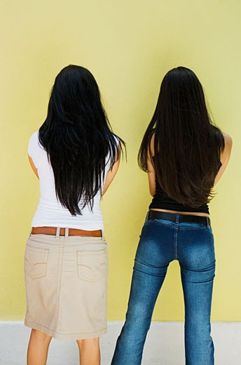 Stock Photo: 1757R-1247 Two young women standing against wall