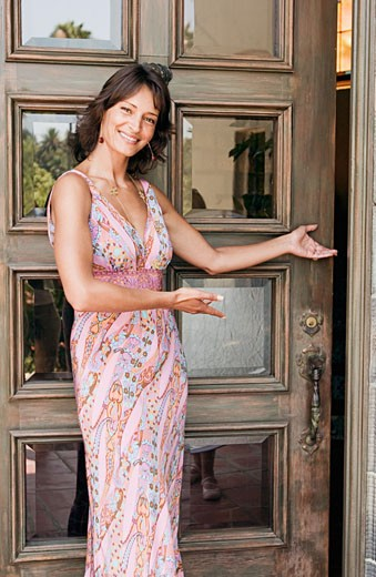Stock Photo: 1757R-1259 Woman greeting at door.