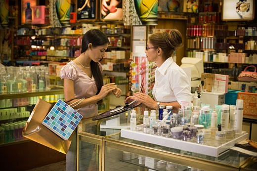 Woman sampling products at beauty counter : Stock Photo