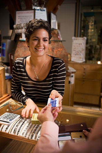 Young woman helping customer in jewelry store : Stock Photo