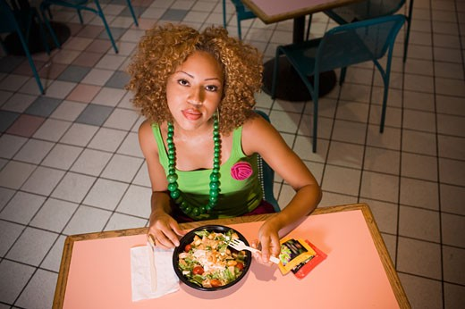 Young woman eating salad in food court : Stock Photo
