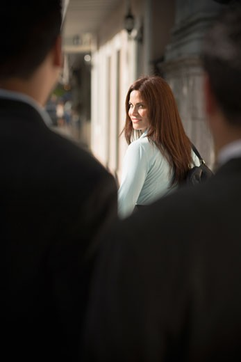Woman walking away from businessmen : Stock Photo