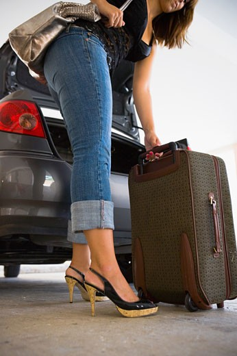 Young woman unloading luggage from car : Stock Photo