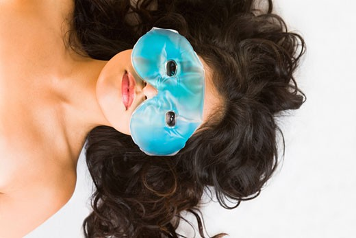 Young woman wearing gel mask on eyes : Stock Photo