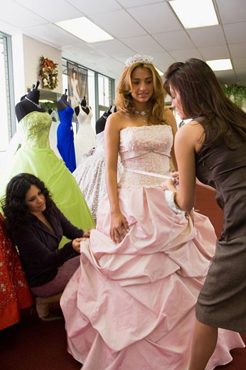 Salesgirl taking measurements on teenage girl in party dress : Stock Photo