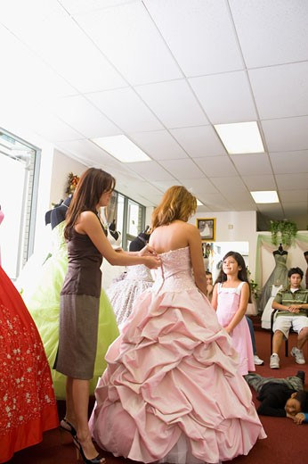 Salesgirl zips up teenage girl's party dress, little sister looks on : Stock Photo