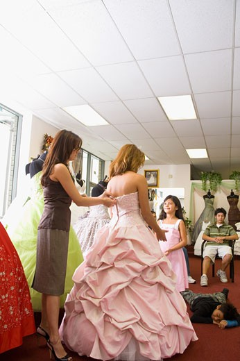 Stock Photo: 1757R-3409 Salesgirl zips up teenage girl's party dress, little sister looks on