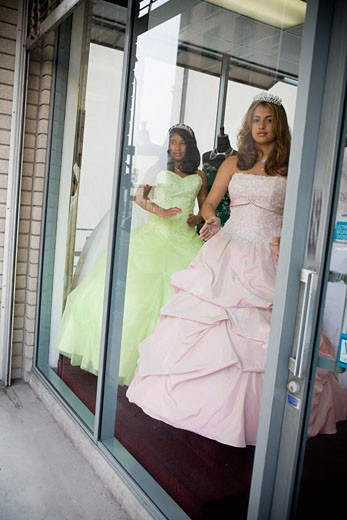 Girls posing as mannequins in dress shop window : Stock Photo