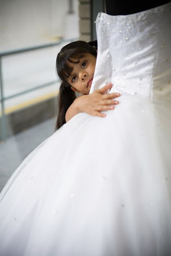 Young girl looks peeks out from behind white gown : Stock Photo