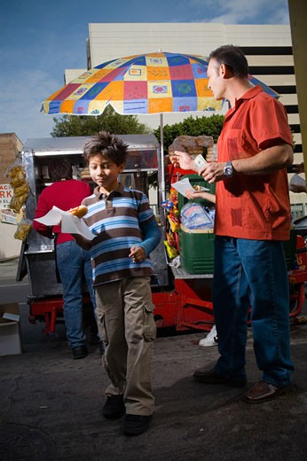 Father and sons eat hot dogs from street vendor : Stock Photo