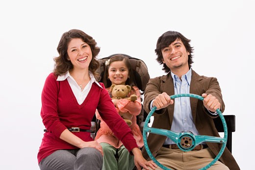 Studio portrait of happy family in imaginary car : Stock Photo