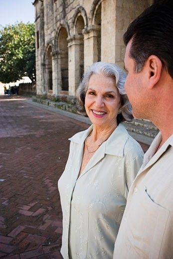Senior woman smiling and standing with her son : Stock Photo